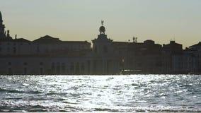 落日闪烁的光在河,组成地平线的屋顶反射了 股票录像