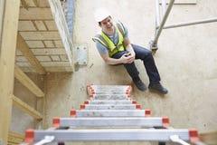 落梯子和腿受伤的建筑工人 免版税库存图片