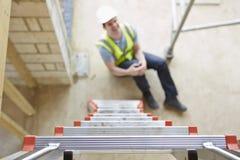 落梯子和腿受伤的建筑工人 免版税图库摄影