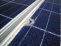 落的子弹打破的太阳电池板在框架附近 免版税库存图片
