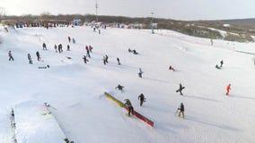 落的挡雪板和的滑雪者天线滑在多雪的倾斜下和做把戏 股票视频