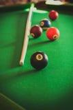 落袋撞球球和棍子在台球台上 图库摄影