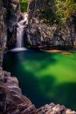 落通过岩石和形成深刻的lak的美丽的瀑布 库存照片