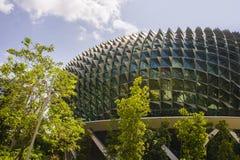 著名和惊人的新加坡歌剧剧院,与位于小游艇船坞海湾的一个惊人的未来派设计的一个大厦的看法 免版税库存图片