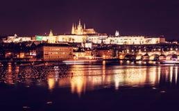 著名城堡和查尔斯在伏尔塔瓦河河,布拉格,捷克共和国跨接反映 城市点燃晚上场面 目的地玻璃扩大化的映射旅行 顽皮地 免版税库存图片