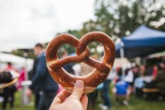 著名德国啤酒节日人在他的手上举行一个传统椒盐脆饼叫的慕尼黑啤酒节庆祝 免版税库存照片