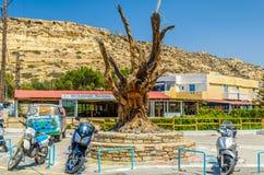 著名树、嬉皮公共汽车和摩托车在Matala集中 免版税库存照片