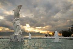 著名海豚雕象在一个池塘有在日落期间的多云天空背景 免版税库存照片