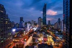 著名玛哈洛坤塔的都市风景在曼谷,泰国 在街道的轻的足迹从汽车 免版税库存照片