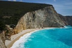 著名空的古希腊海滩在与绿松石闪耀的海的一个晴朗的春日在木质的峭壁下 库存照片