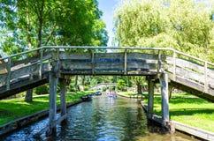 著名羊角村村庄看法有运河和土气茅屋顶房子的 图库摄影