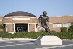 著名足球运动员雕象在大学大厦前面的 库存照片