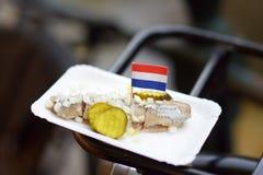 著名鲱鱼用葱和黄瓜在自行车树干在阿姆斯特丹,荷兰 免版税库存图片
