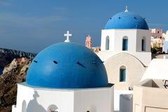 著名3个蓝色圆顶的被弄脏的图象在圣托里尼的 库存照片