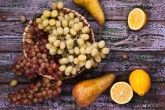 葡萄、梨和limons在紫色背景 库存图片