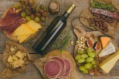 葡萄、白葡萄酒、乳酪、蜂蜜和坚果在被风化的土气 图库摄影