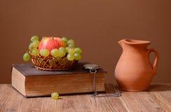 葡萄、苹果、书和陶瓷玻璃水瓶 免版税库存照片