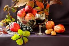 葡萄、苹果、坚果和一杯红葡萄酒和绿色叶子 库存照片