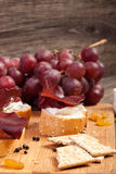 从葡萄、薄脆饼干和火腿的混杂的开胃小菜 库存照片