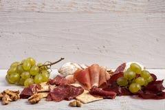 从葡萄、薄脆饼干和火腿的混杂的开胃小菜 库存图片