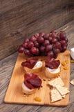 从葡萄、薄脆饼干和火腿的混杂的开胃小菜 免版税库存图片