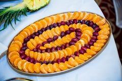 葡萄和切的蜜桔盘子  图库摄影