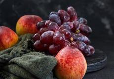 葡萄和桃子在黑暗的背景 免版税库存照片