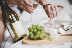 葡萄和瓶与乳酪盘子的白葡萄酒午餐的在卧室 免版税图库摄影