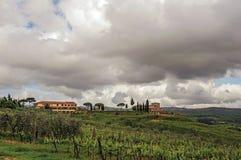 葡萄园和小山概要与别墅在上面在托斯坎乡下 免版税库存照片