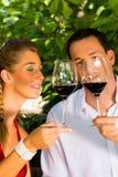 葡萄园饮用的酒的妇女和人 免版税库存图片
