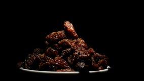 葡萄干或葡萄干果子食物在回旋在黑背景的碗 影视素材