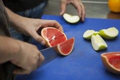 葡萄柚切口厨师的手 免版税库存图片