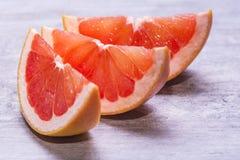 葡萄柚切片,水多成熟在灰色背景 免版税库存图片
