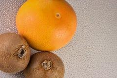 葡萄柚和两个猕猴桃在塑料厨房上 图库摄影