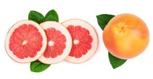 葡萄柚和切片与在白色背景隔绝的叶子 顶视图 平的位置样式 免版税库存照片