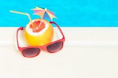 葡萄柚和太阳镜在游泳池边缘  免版税图库摄影