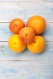 葡萄柚和桔子在一个蓝色木板,顶视图 图库摄影