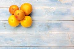 葡萄柚和桔子在一个蓝色木板,顶视图 库存照片