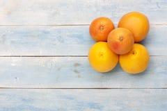 葡萄柚和桔子在一个蓝色木板 库存图片
