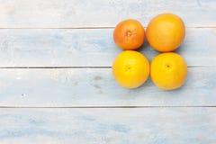 葡萄柚和桔子在一个蓝色木板 免版税库存照片