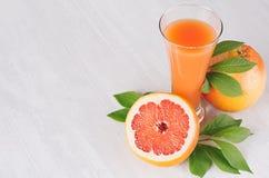 葡萄柚夏天明亮的新鲜的桃红色鸡尾酒与绿色叶子的,在白色木背景的切片葡萄柚 库存图片