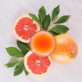 葡萄柚夏天明亮的新鲜的桃红色鸡尾酒与绿色叶子的,在白色木背景,顶视图,正方形的切片葡萄柚 库存照片