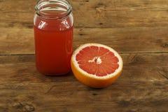 葡萄柚汁和新鲜的葡萄柚在木背景 在一个玻璃碗的新鲜的葡萄柚汁 免版税库存照片