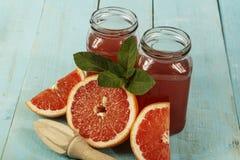 葡萄柚汁和新鲜的葡萄柚在木背景 在一个玻璃碗的新鲜的葡萄柚汁 免版税库存图片