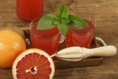 葡萄柚汁和新鲜的葡萄柚在木背景 在一个玻璃碗的新鲜的葡萄柚汁 库存图片
