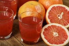 葡萄柚汁和新鲜的葡萄柚在木背景 在一个玻璃碗的新鲜的葡萄柚汁 免版税图库摄影