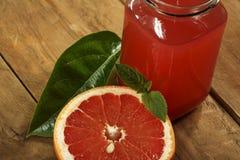 葡萄柚汁和新鲜的葡萄柚在木背景 在一个玻璃碗的新鲜的葡萄柚汁 库存照片