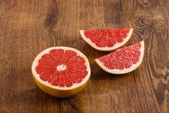 葡萄柚片断在木桌上的 免版税库存图片