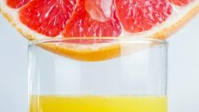 葡萄柚的宏观图象clive在杯新鲜的汁液 图库摄影