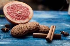 葡萄柚,桂香,在葡萄酒的麦甜饼深蓝木背景 免版税库存照片